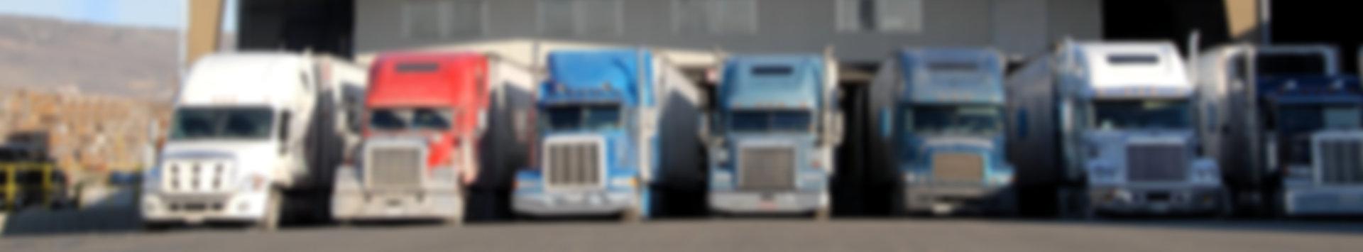 seven semi trucks at warehouse waiting to be loaded